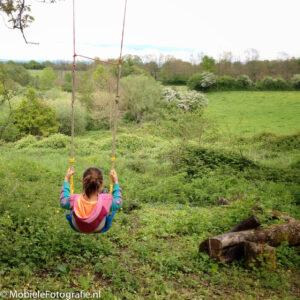 Regel van derden: de horizonlijn ligt op een derde vanaf de bovenzijde en het schommelende meisje ligt op een sterk punt.