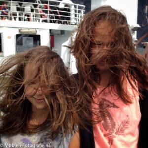 Mobiele foto van kinderen met haar in de wind