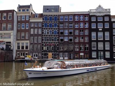 Onderwerp van de foto: rondvaartboot in Amsterdam. Benadrukken: regel van derden, meer ruimte aan voorkant dan aan achterkant, Amsterdamse huizen als achtergrond, boot volledig in beeld. [iPhone 4s]