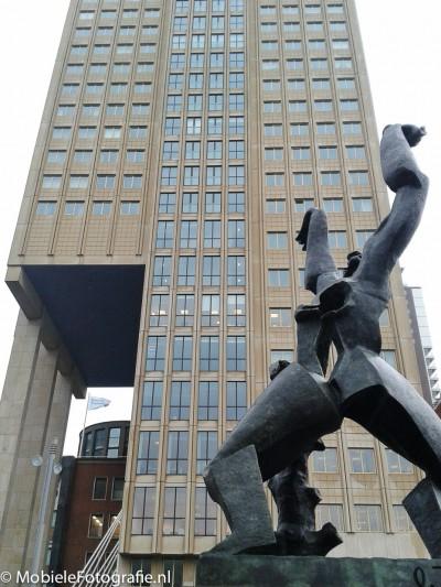 Onderwerp van de foto: beeld 'De verwoeste stad' van Zadkine. Benadrukken: van onderaf gefotografeerd, hoog gebouw als achtergrond, geen verstoring door de rest van de stad.