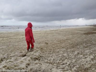 Onderwerp van de foto: meisje op het strand met algenschuim Benadrukken: kleur van de kleding, ruimte voor de persoon. [iPhone 4s]