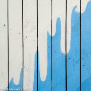 Wit-blauw geverfd hout, detail van een wandschildering gefotografeerd met een Samsung Galaxy Trend