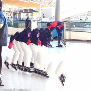Een schaatser die een aantal keer op een panoramafoto wordt afgebeeld.