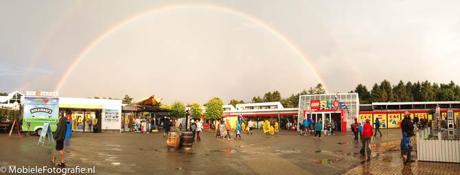 Panoramafoto van Legoland in Denemarken, met een regenboog. De persoon die linksonder loopt is op de foto hieronder uitvergroot weergegeven.