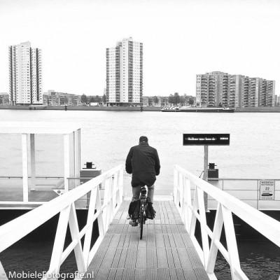 Foto van leidende lijnen richting een fietser op een bruggetje in Rotterdam. [Lumia 640 LTE]