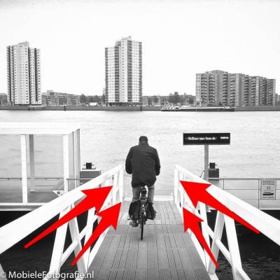 Leidende lijnen door een brugleuning richten je blik op de fietser.