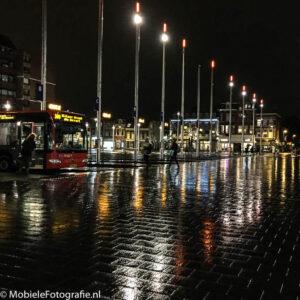 Foto van de Lichten van het busstation in Haarlem die reflecteren in de natte straat. [iPhone 6]