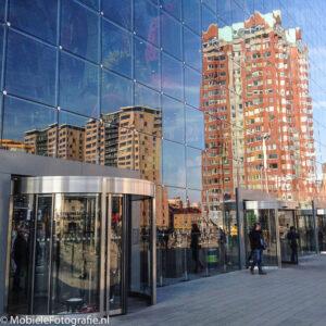 Foto van de glazen gevel van de Martkhal in Rotterdam die de omgeving reflecteert. [iPhone 6]