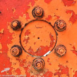 De regel van symmetrie toegepast op een detail: het oranje wiel van een oude tractor [iPhone 6]