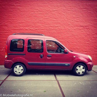 Voorbeeldfoto van Monochromatische kleuren: een rode auto voor een rode muur. [iPhone 4s]
