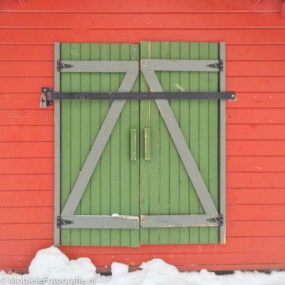 Voorbeeldfoto van Complementaire kleuren: een groene deur in een rode muur. [iPhone 6]